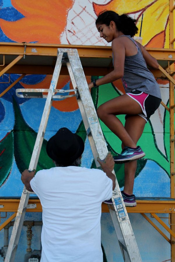 Mr.Olais+helps+senior+Lylia+Fernandez+safely+climb+the+ladder+onto+the+lift.+