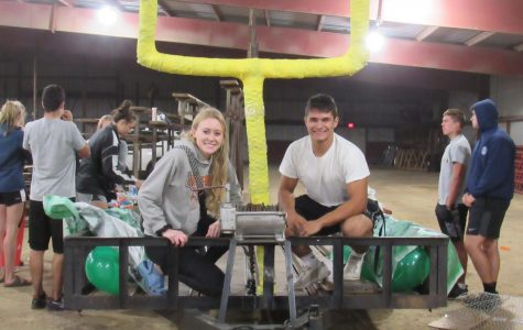 After hours of working, Seniors Aspen Olson and Matt Seirer pose in front of their finished product.