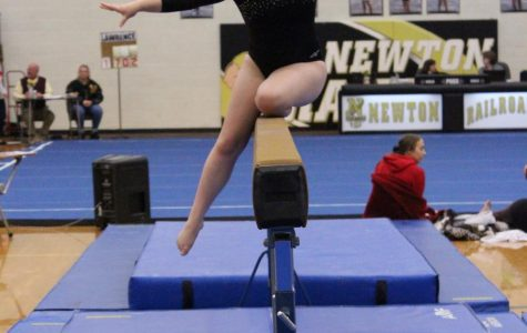 Junior Becca Meyer finishes her back roll on the beam.