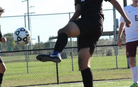 WIth his foot in the air, sophomore Gerardo Torres attempts to kick a goal.