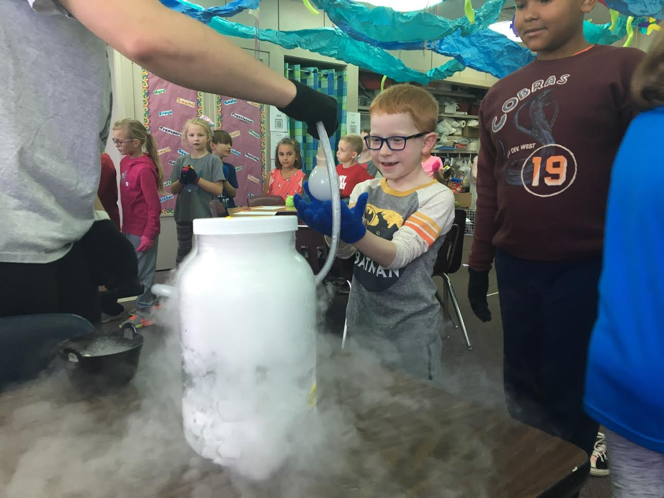 Students interact with experiment demonstrated by Chemistry Club students