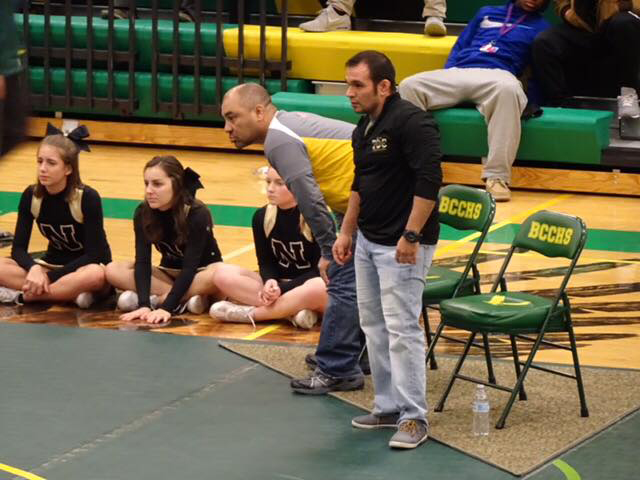 Wrestling coaches J.J. Thaw and Tommy Edgmon watch and advise wrestlers during a match. Thaw died just before the state tournament last year; wrestlers are preparing for a season without their long-time assistant.