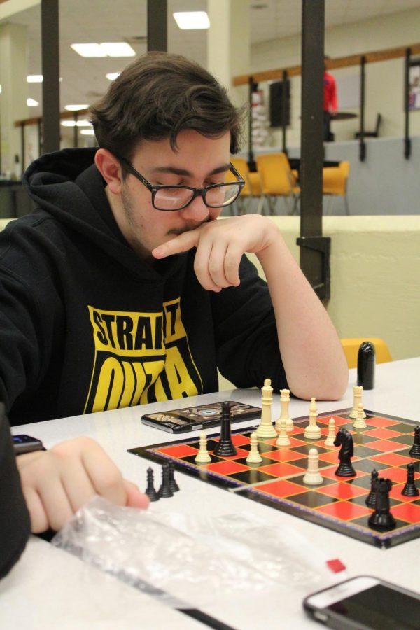Junior Jaden Degrado observes his chess board for a possible move.