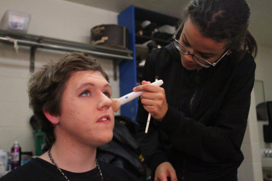 Backstage, sophomore Caitlynn Erickson applies make-up on junior Rai Angolo for his role as Judas. Students in the Tech Theater class assisted actors in preparing for stage.