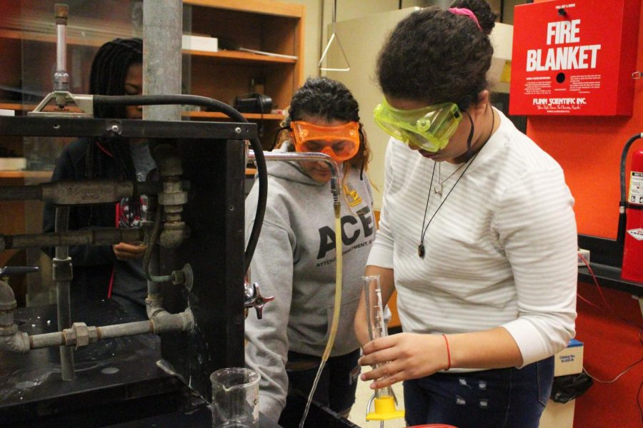 Juniors Ebony Tilden and Ariani Nunez clean off their graduated cylinders after finishing the lab.
