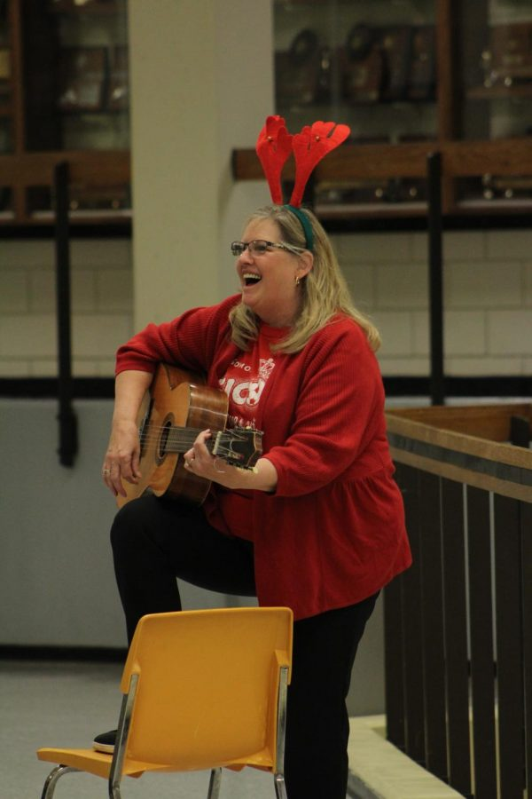Smiling, Spanish teacher Cheryl Loeffler sings 'Feliz Navidad' with Spanish club.
