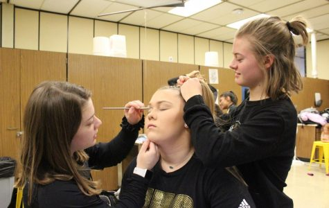 Working together, junior Becca Meyer and sophomore Madyson Groves help junior Reagan Moe get ready for their performance.