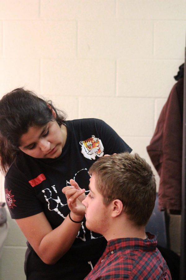 Putting+makeup+on+sophomore+Tristan+Mitchell%2C+junior+Alejandra+Llamas+dabs+at+his+concealer+%0A