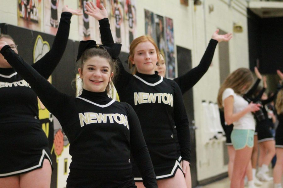 Finishing a cheer, juniors Becca Meyer and Lindsey Voth wave to the crowd.