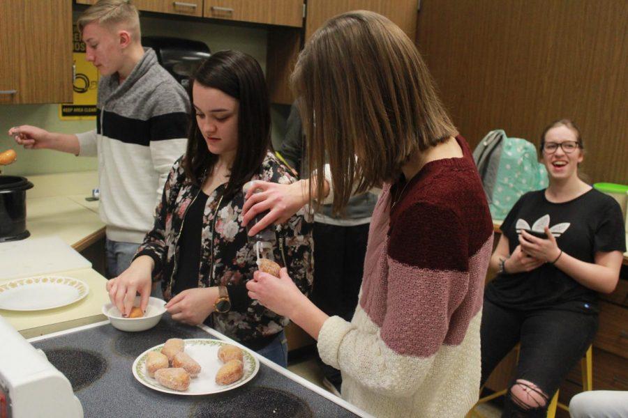 Junior Emily Penner adds jelly filling inside the donut.