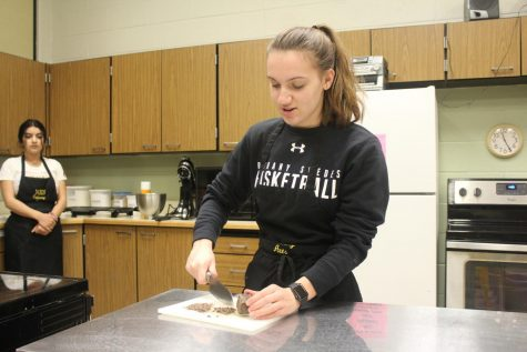 In place of chocolate chips, senior Megan Bartel cuts up chocolate.