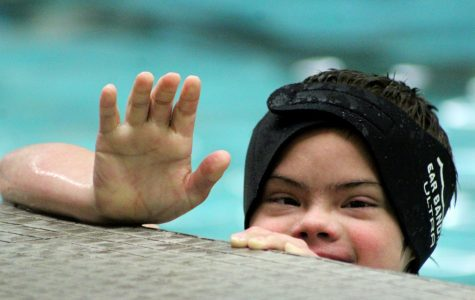 Student from middle school waves from the side of the pool.