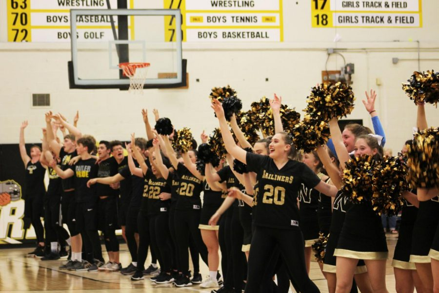 Raising their hands, junior Chandlor Buffalo, the Railiners, Mailiners and Cheer squad sing the alma mater.