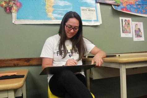 Freshman Olivia Sandoval writes on a whiteboard.