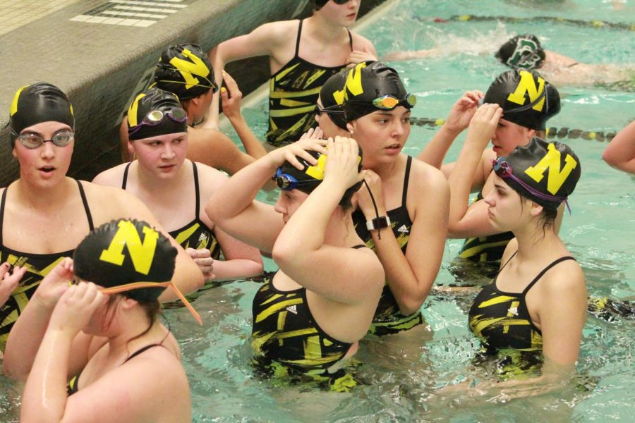 The girls stand together at the side of the pool before their warm up.