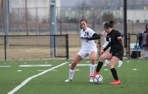 Sophomore Arianna Campos keeps the ball away from the Buhler defender.