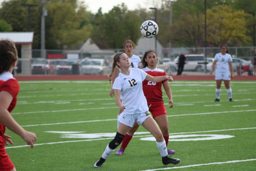 Playing forward, freshman Adeline Tonn heads the ball away from a McPherson player.