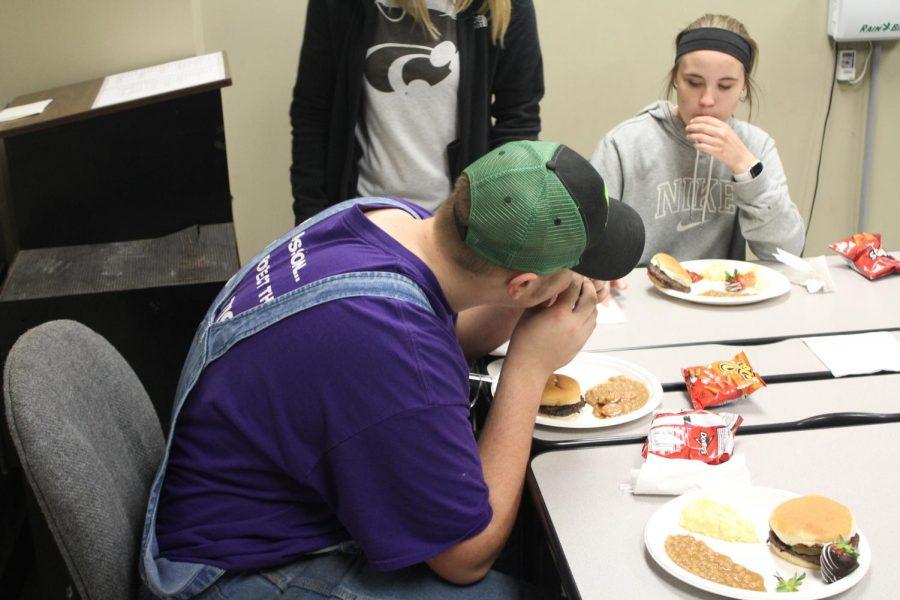 Sophomore Drake Hamm takes a bite of a hotdog.