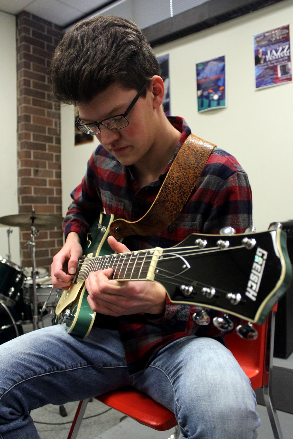 Practicing his electric guitar, senior Seth Bontrager plays tunes in the jazz room during seminar on Jan. 17. Seth practices anywhere from an hour to two hours a day. Photo Credit Emily Brandt