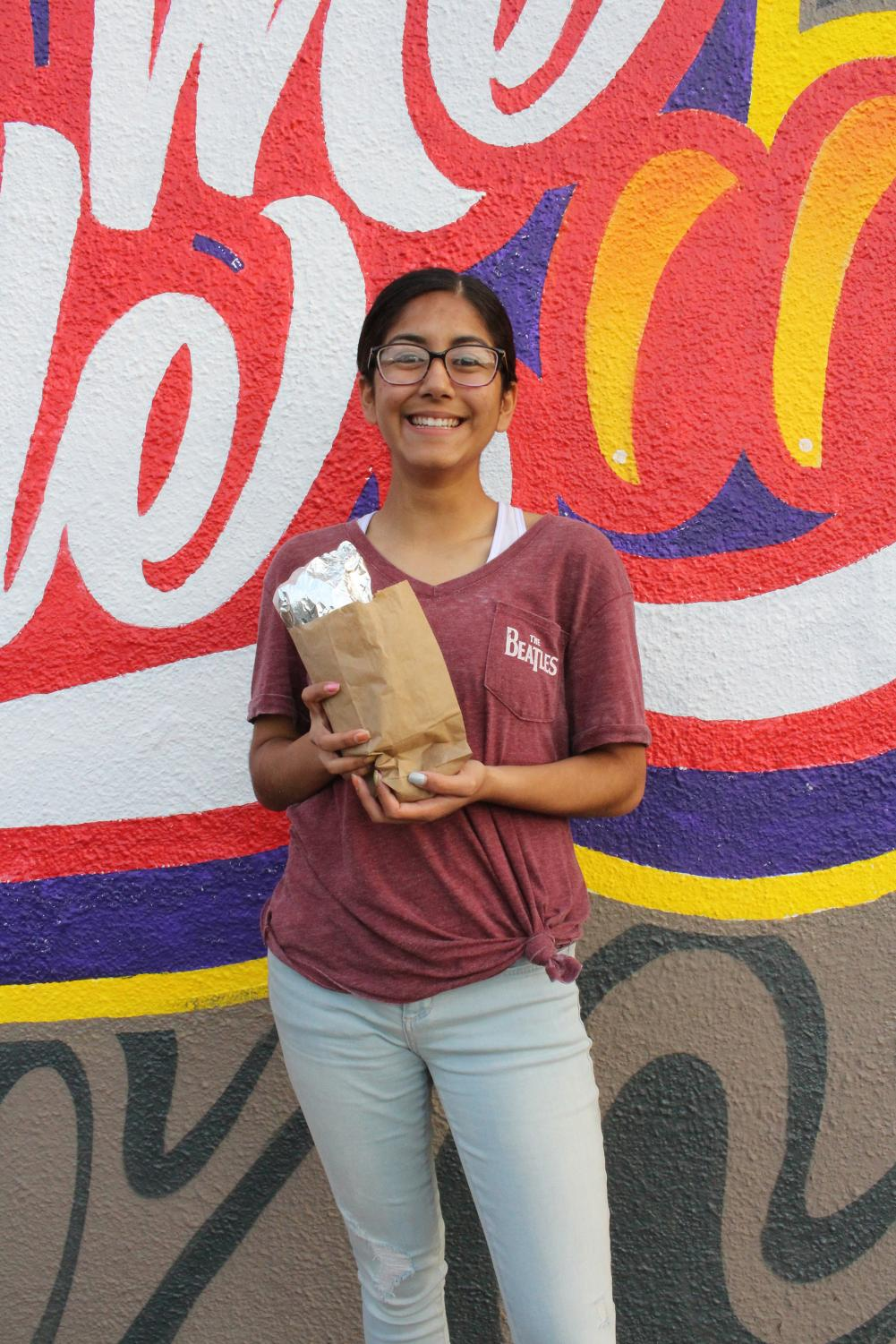 Senior Lylia Fernandez stands outside Kiko's with one of their signature carne asada burritos.