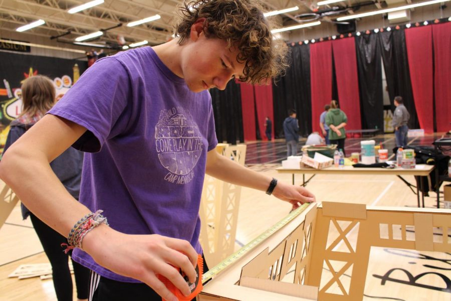 """Junior John Jantzen measures the distance of the base to replicate the mini tower of Paris in Vegas for prom. This year's theme was a """"Viva Las Vegas"""" and took place on April 13 in Ravenscroft Gym."""
