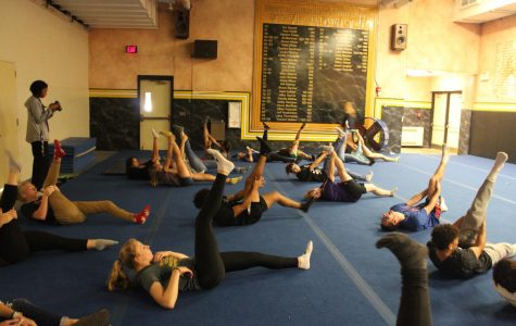 At the beginning of the club meeting, the students stretch their legs in order to do yoga poses.