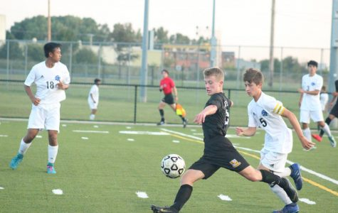 Gliding into the ball, freshman Collin Hershberger attempts a kick to push the team further down the field.