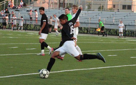 Kicking it far out junior Alex Sanchez.