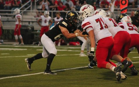 As the opposing team rushes, junior Davis Mick blocks against his man.