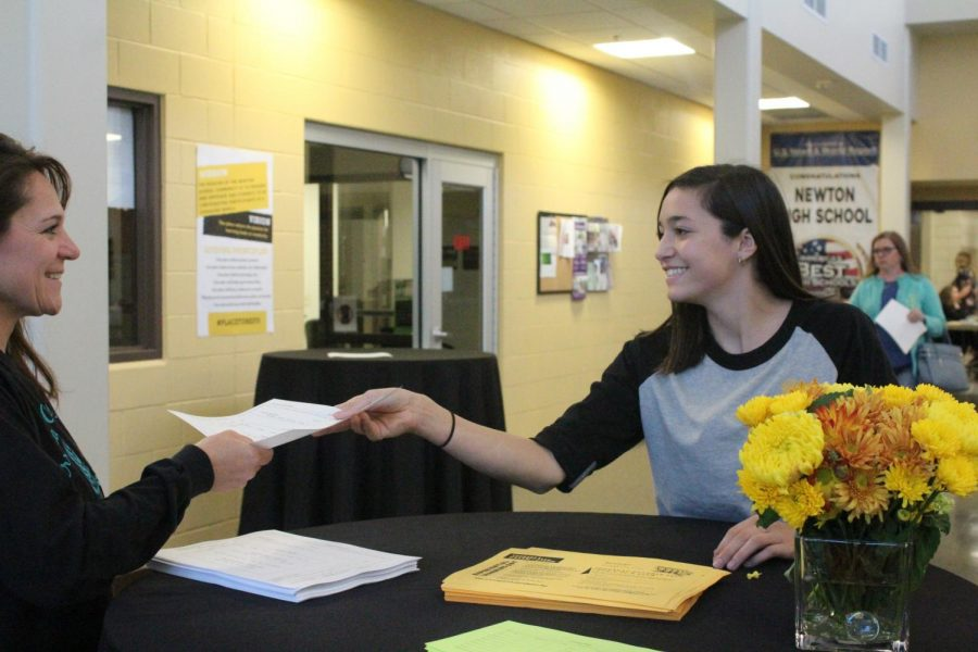 Junior Savannah Garcia hands out a paper from the STUCO welcoming table to a parent.