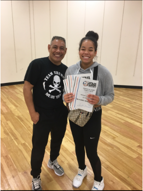 Junior Maylee Edwards stands with her MMA coach, Chris Rangel, holding her first place awards
