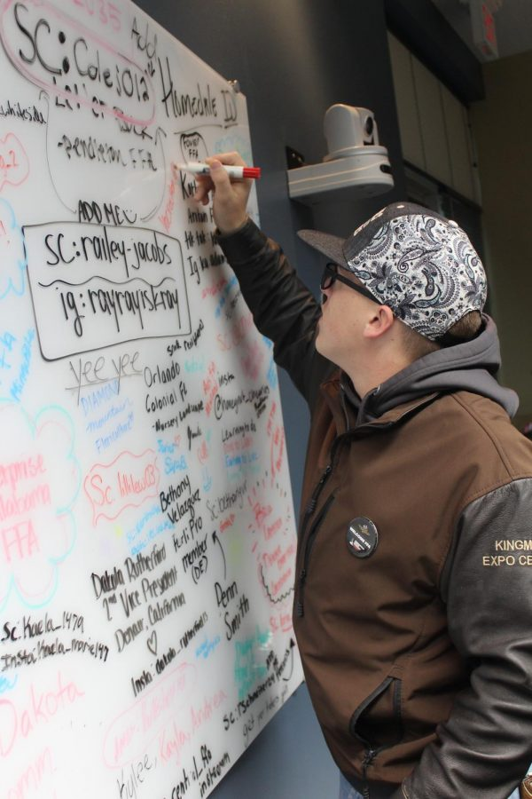 Junior Keaton Benedick signs the whiteboard at National FFA Headquarters.