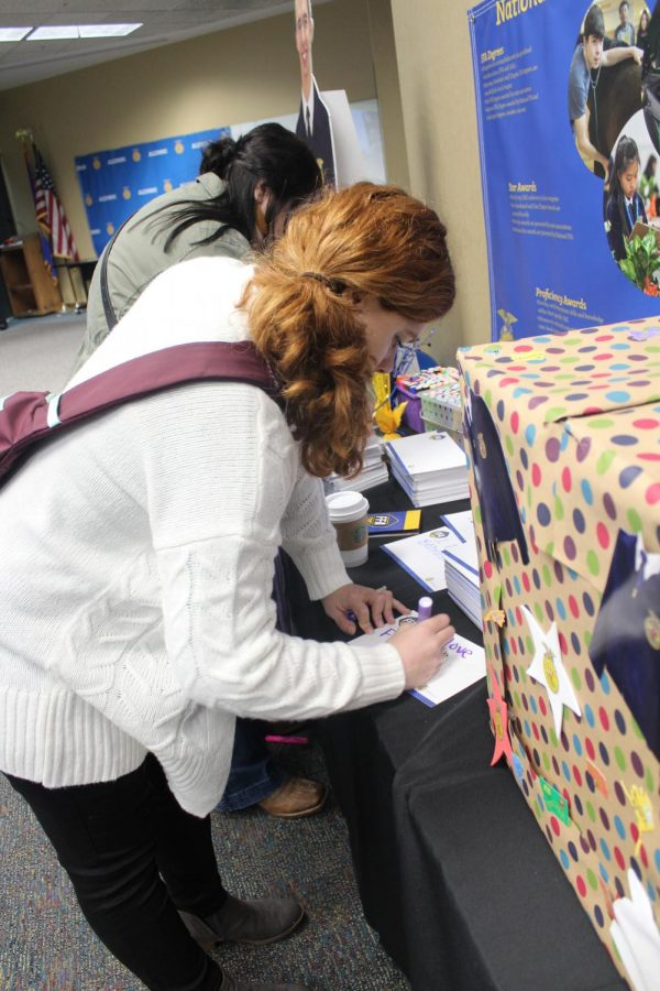 Ag teacher/ FFA advisor Paxton Trembly writes her answer to a question on a sheet of paper to drop into a box.
