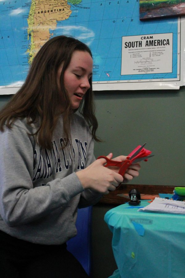 Sophomore Jamie Prine cuts tissue paper for a project.