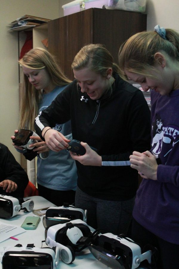Sophomores Mckennah Cusick, Hayley Loewen and Lauren Anton station at the table with VR headsets.