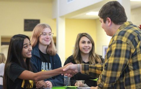 Juniors Alondra Valle and Eli Redington shake hands as Redington comes in to work the table with sophomores Daisy Buller and Jacey Yager.