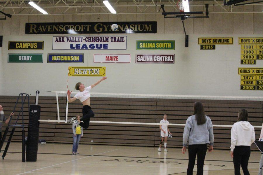 Junior+Benjamin+Schmidt+jumps+up+to+spike+the+ball.