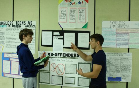 Sophomore Kenyon forest presentates his poster to sophomore Joe Slechta.