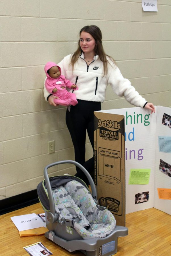 Senior Madison Edison holds an infant simulator that the FACS pathway uses.