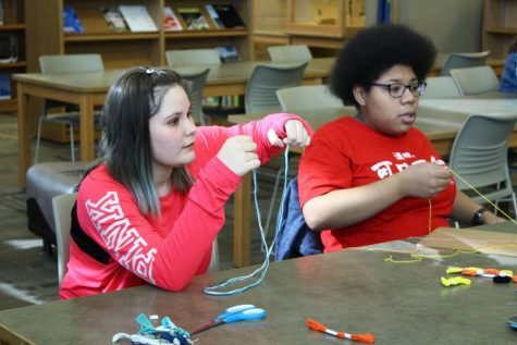 Freshmen Madison Hershberger and Isabel Madrigal choose the string they want to create their bracelets during friendship bracelet club.