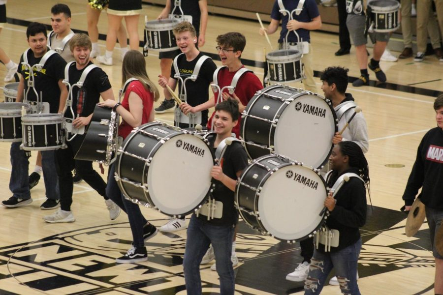 Students in the drumline walk off the court after performing in front of the student section.