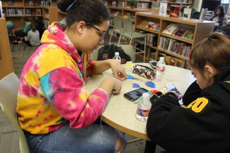 Using tape to hold down her string, senior Ebony Tilden makes a friendship bracelet during first clubs on Nov. 8 of last year. Friendship Bracelet Making Club has only met three times this school year.