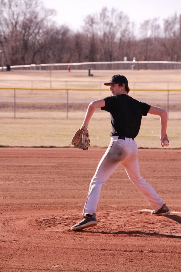 Junior+Griffin+Davis+pitches+while+others+practice+a+drill.+