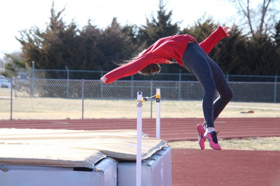 Reaching over the bar, junior Asha Regier practices high jump.