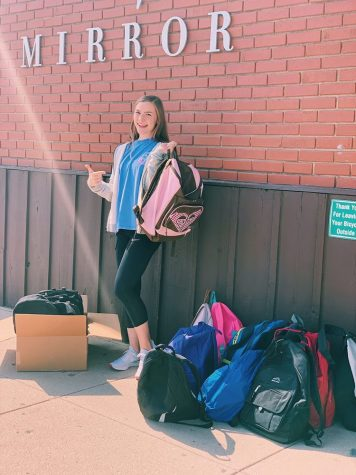 "Smiling at the camera, freshman Gracie Hendrickson poses with a ""fresh start"" backpack."