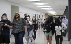 While wearing masks, students and staff walk through the halls before seminar on Sept. 22.