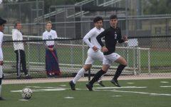 Keeping his eye on the ball, sophomore Ezra Entz runs down the field.