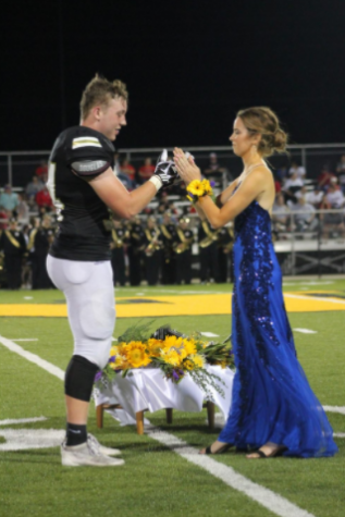 Alumni Drake Henrich and Maddie Edson preform their handshake in front of the crowd in the 2019 homecoming.