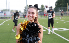 In order to support the team senior Cecilia Merlini cheers to the crowd. Merlini is the first foreign exchange student to be on the cheer team.
