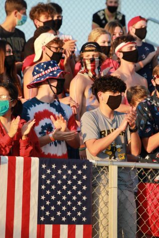 Following the new guidelines put in place, students cheer for the football team while wearing masks to stop the spread of COVID-19.